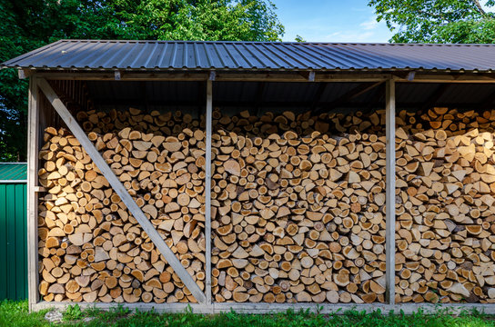 Wooden background. Firewood drying for the winter, stacks of firewood