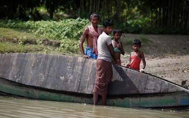 A man and his sons repair their boat at Patamari village near the international border between India and Bangladesh