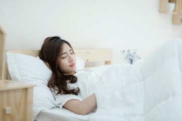 A beautiful young woman sleeping in bed. Happy morning. Portrait of a smiling pretty young lady relaxing in white bed.