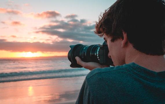 Filmmaker at the beach shooting sunset