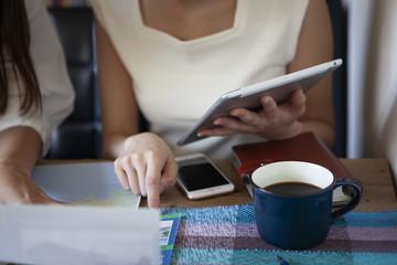 タブレットと地図を見ながら旅行先をチェックしている女性たち