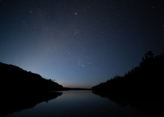 The fading stars in the early morning sky are reflected in a quiet lake and one small meteor from the Perseid meteor shower streaks across minutes before the daylight renders them invisible.
