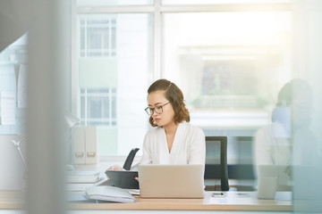 Young female entrepreneur busy with work on tablet computer