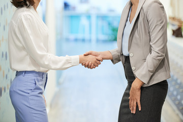 Cropped image of business women shaking hands in office corridor
