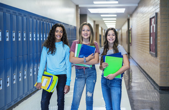 Group of Junior High school Students standing together in a school hallway. Female classmates smiling and having fun together during a break at school