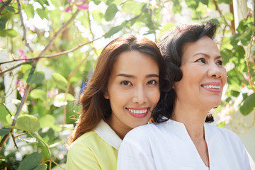 Happy beautiful young Asian woman with senior mother in summer blooming garden