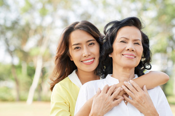 Portrait of happy senior Vietnamese woman and her adult daughter hugging in summer park