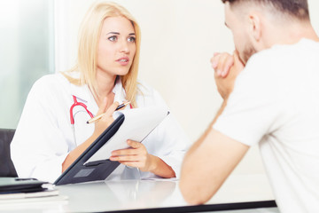Woman Doctor and Male Patient in Hospital Office