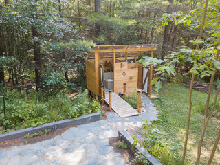Aerial drone shot of an outdoor shower and composting toilet stall at a glamping site