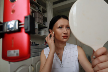 """Makeup artist He Yuhong checks her makeup during a recording of her transformation into the """"Girl with a Pearl Earring"""" at her house in Chongqing"""
