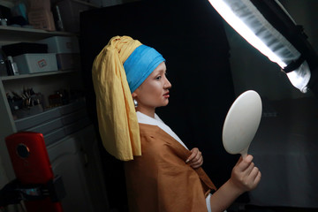 """Makeup artist He Yuhong checks herself in the mirror during a photo shoot following her transformation into the """"Girl with a Pearl Earring"""" at her house in Chongqing"""