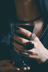 Witch holds a magic black chalice. Silver rings with semi-precious stones on her hand. Close up shot. Gothic style and witchcraft concept.