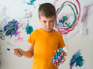 A little boy of 5 years with a guilty look painted with paint and brush on the wall of his room. Naughty child, angry baby