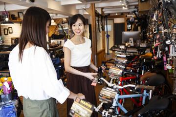 店員と一緒に自転車を選ぶ女性
