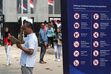 A man stands next to a sign showing prohibited items at a gate of the Gelora Bung Karno sports complex, ahead of the 2018 Asian Games in Jakarta