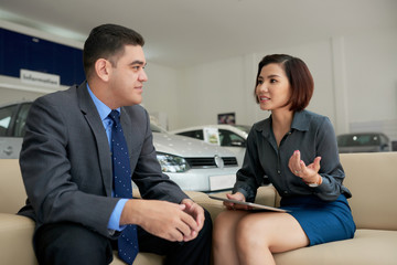Young Vietnamese female car dealer consulting customer