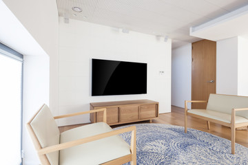 television with wood chair in a white interior