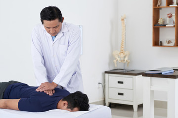 Professional Vietnamese chiropractor doing pushing motion to adjust spine of male patient