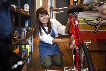 自転車の状態を確認する女性とスタッフ
