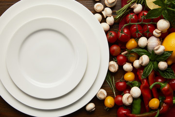 top view of empty round white plates and fresh vegetables on wooden surface