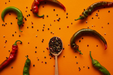 top view of chili peppers and peppercorns in wooden spoon on orange