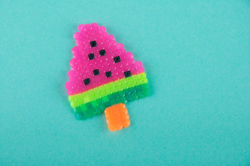 Funny plastic ice cream in shape of watermelon on stick laying on blue background