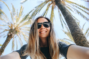 Young beautiful woman tourist or blogger makes a selfie or is reporting to its subscribers on the background of palm trees in a hot country.
