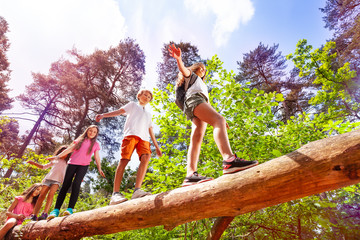 Group of kids walk over big log in the forest Wall mural