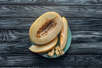 top view of sweet ripe sliced melon on plate on wooden surface