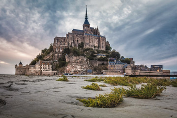 Beautiful view of famous historic Le Mont Saint-Michel tidal island with sandy and grass foreground, France