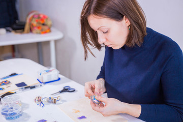 Professional jewelry designer making handmade brooch with beads in studio, workshop. Fashion, creativity and handmade concept