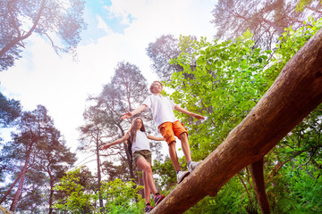 Boy and girl walks over the high log in forest