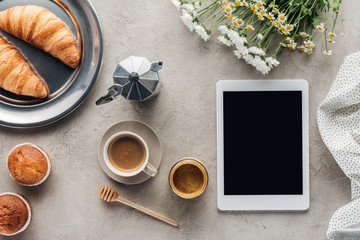 top view of coffee with pastry and tablet with blank screen on concrete surface