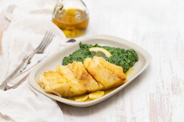 fried cod fish with spinach on dish