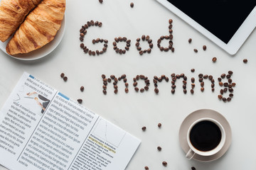 top view of cup of coffee and good morning lettering made of coffee beans on white surface with croissants, newspaper and tablet
