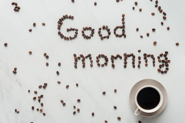 top view of cup of delicious coffee and good morning lettering made of coffee beans on white marble