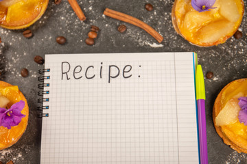 sweet cake, cinnamon, coffee grains and a notebook for a recipe lie a gray stone background