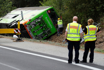 Police officers inspect a crashed Flixbus bus on the side of the A19 highway, in Linstow