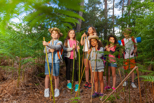 Group of kids stand in forest resting during hike