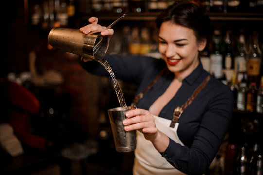 Beautiful sexy smiling barmaid making a fresh summer cocktail