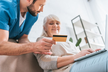 social worker holding credit card and looking at senior woman using laptop