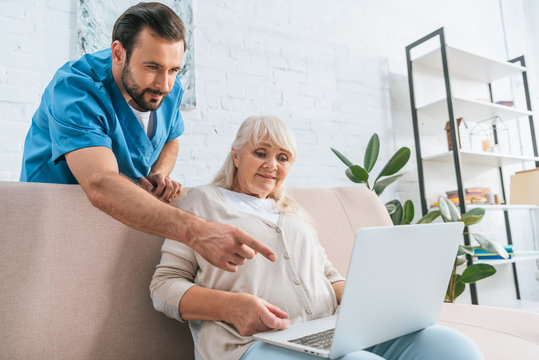 young male social worker pointing with finger at laptop white senior woman sitting on couch