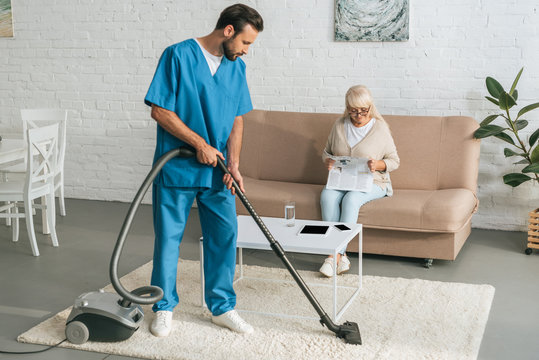 young social worker cleaning carpet with vacuum cleaner while senior woman reading newspaper on couch