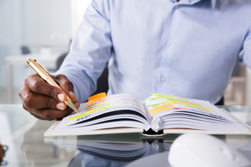Fototapete - Businessman Writing Schedule In Diary With Pen
