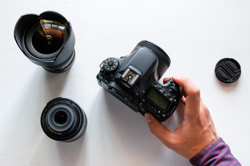 A man holds a camera near various lenses. world day of photography