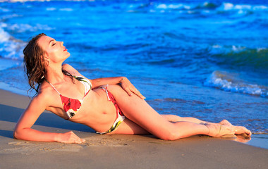 Sexy gorgeous woman with beautiful slim body is posing on a sandy sea beach, summer holidays concept, pretty girl