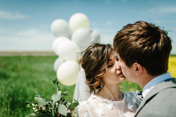 The happy bride and groom hold the balloons and stand after wedding ceremony. A newlywed couple hugging and kissing on a country road in their honeymoon. photo.