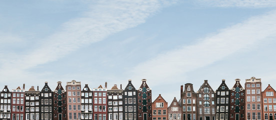 Aluminium Prints Amsterdam Panorama or panoramic view. Traditional houses in Amsterdam in the Netherlands in a row against the blue sky.