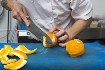 Chief cut orange fruits on chopping board