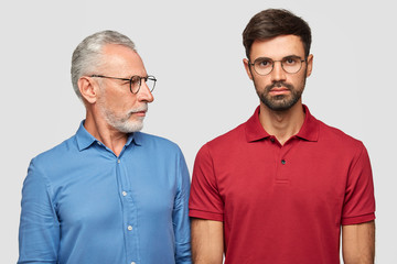 Elderly experienced male looks attentively at his adult son, gives pieces of advice, wears spectacles and formal blue shirt, have good relations. People, age, lifestyle and life experience concept